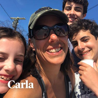 Carla standing in the middle of her three kids while taking a selfie