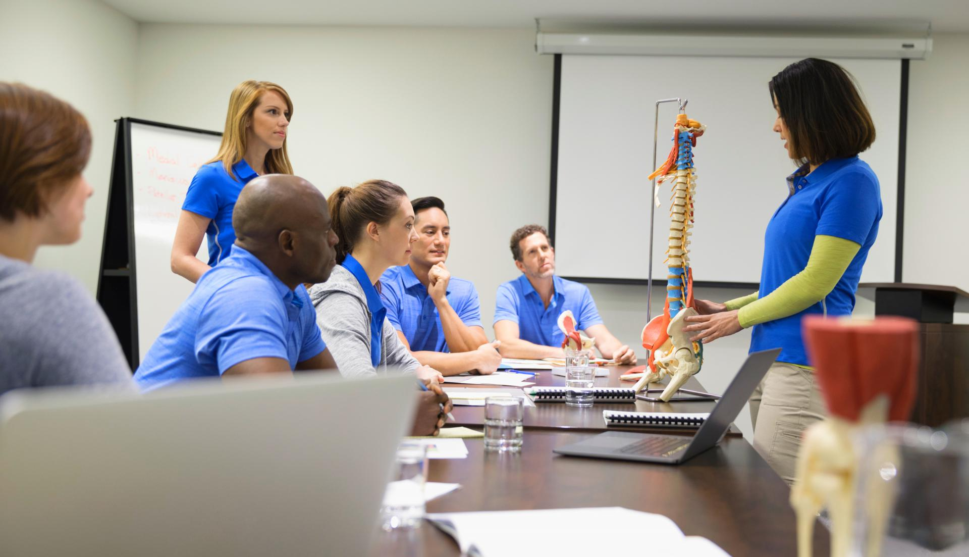 Professor and students in class looking at a model of a spine.