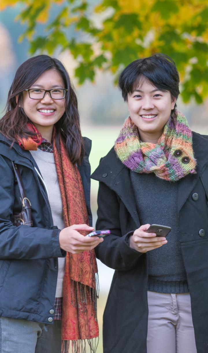 Two women wearing scarves and coats holding their cell phones.